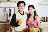 Portrait of a young man standing with a mid adult woman in the kitchen