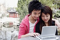 Close-up of a teenage boy and a young woman using a laptop