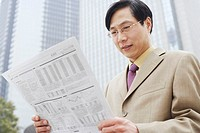 Close-up of a businessman reading a newspaper