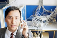 Portrait of a businessman using a telephone in a server room