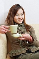 Close-up of a young woman holding a cup of tea smiling