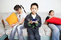 Portrait of a boy playing a video game beside his two sisters