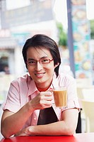 Portrait of a mid adult man sitting in a cafe and holding a mug of coffee