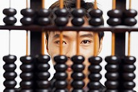 Portrait of a businessman behind an abacus
