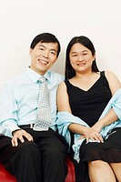Portrait of a businessman and a mid adult woman sitting together on a couch and smiling