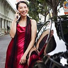Businesswoman leaning against a car and talking on a mobile phone