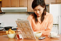 Close-up of a young woman reading a newspaper at a kitchen counter