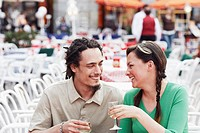 Young couple sitting together at a sidewalk cafe