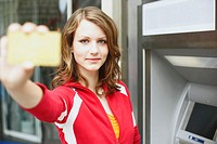 Portrait of a teenage girl holding an ATM card