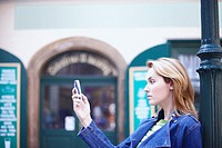 Side profile of a young woman holding a mobile phone