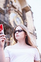 Low angle view of a young woman holding a mobile phone