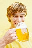 Portrait of a young man holding a glass of beer