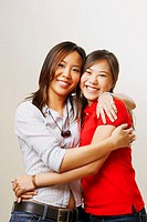 Portrait of two young women hugging each other and looking cheerful