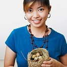 Portrait of a young woman holding eggs in a bird's nest and smiling