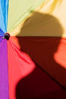 Close-up of a person's shadow on a colorful umbrella