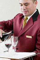 Close-up of a waiter pouring red wine into wineglasses