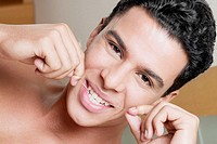 Portrait of a young man flossing his teeth