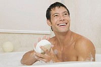 Close-up of a young man holding a loofah in a bathtub