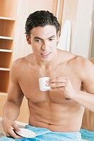 Close-up of a young man drinking a cup of tea