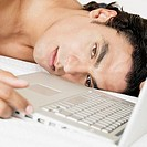 Close-up of a young man lying near a laptop