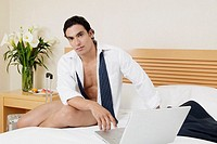 Portrait of a young man sitting on the bed with a laptop