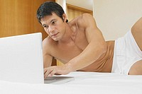 Mid adult man lying on the bed and using a laptop