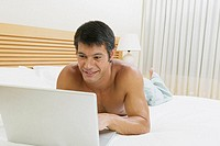 Close-up of a mid adult man lying on the bed using a laptop