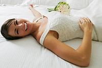 High angle view of a bride lying on the bed and smiling