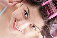 High angle view of a young woman putting on hair curlers and smiling