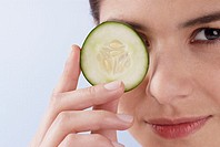 Portrait of a young woman covering her eye with a cucumber slice