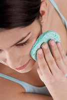 High angle view of a young woman scrubbing her face with a sponge