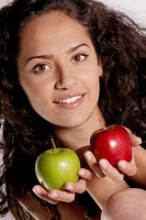 Portrait of a young woman holding two apples