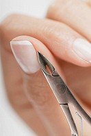 Close-up of a woman's hand using a nail scissor