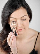 High angle view of a young woman using an eyelash curler
