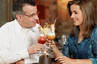 Close-up of a mid adult couple sitting in a restaurant and toasting glasses of pina colada