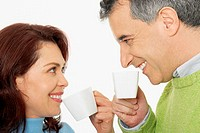 Close-up of a mid adult couple holding tea cups and smiling