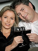 Portrait of a mid adult woman and a mature man toasting glasses of red wine and smiling (thumbnail)