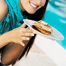 Close-up of a young woman holding waffles in a plate
