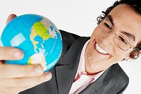 Close-up of a businessman holding a globe and smiling
