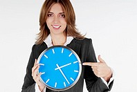 Portrait of a businesswoman pointing at a clock and smiling