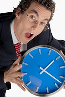 Portrait of a businessman holding a clock