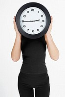 Businesswoman hiding her face with a clock