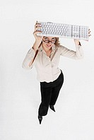 High angle view of a businesswoman holding a computer keyboard over her head