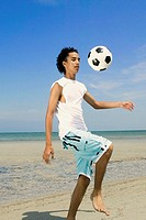 Teenage boy playing with a soccer ball on the beach