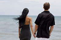 Rear view of a young couple standing on the beach