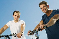 Portrait of two young men smiling and holding bicycles