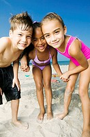 Portrait of two girls and a boy standing on the beach and smiling
