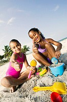 Portrait of two girls playing with sand on the beach