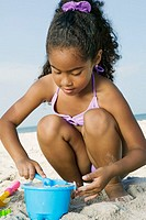 Close-up of a girl playing with sand on the beach