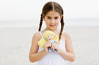 Portrait of a girl standing on the beach and holding a doll
